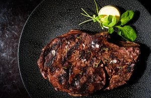 grass fed organic ribeye steak on a black plate with basil and a butter pat