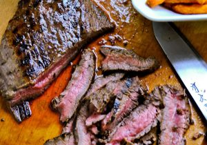 Organic grass fed beef london broil cut into strips on a wooden cutting board