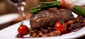 Grass Finished Filet Mignon Steak with cherry tomatoes, bacon wrapped asperagus in a bean sauce